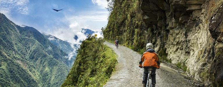 """Bike adventure travel photo. Bike tourists ride on the """"road of death"""" downhill track in Bolivia. In the background sky circles a condor over the scene."""