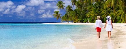 happy loving couple walking on summer tropical beach