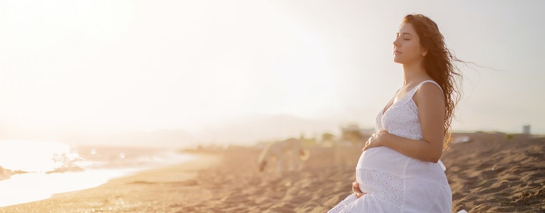 Young beautiful pregnant woman on the beach. Relax by the calm sea in sunshine