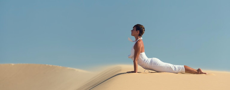 Yoga meditation on the beach, healthy female body in peace, woman sitting relaxed on sand over beautiful sea sunset