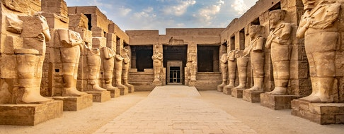 KARNAK TEMPLE - Large sculptures of pharaohs inside landmark with hieroglyphics and ancient symbols. Nile River and Luxor, Egypt