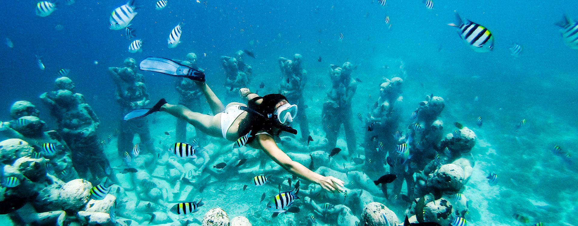 Snorkel woman swimming in a turquoise ocean under the flooded statues. Free diving.