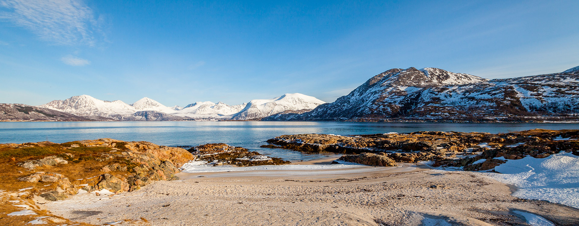 Snowy mountains and bright blue sky in the background. Spring landscape with melting snow and ice. Arctic Circle, Sommaroy, Norway