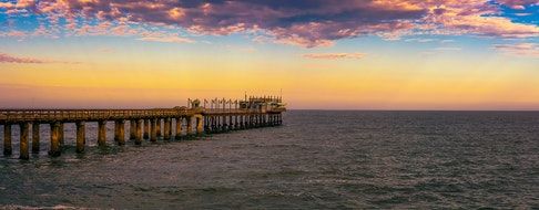 Colorful sunset over the old historic jetty in Swakopmund, Namibia.