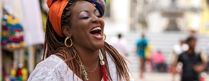 Happy Brazilian woman of African descent dressed in traditional Baiana costumes in the Historic Center of Salvador da Bahia, Brazil