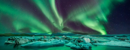 Couple watches the northern lights. Woman and man at winter night landscape . Iceland