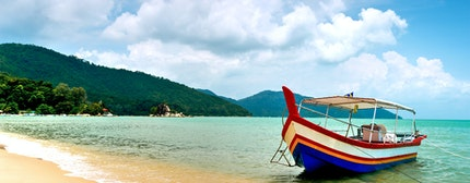 Sunny beach and green mountains with colourful boat in Penang, Malaysia