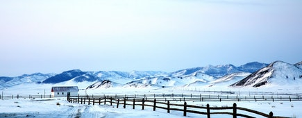 Little White House and wooden fence in a Landscape of northern Mongolia in a winter