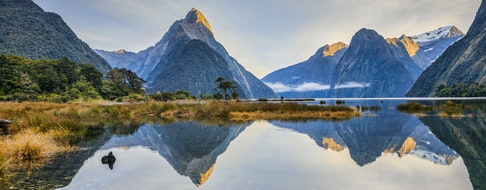 First light on Mitre Peak and surrounding mountains at Milford Sound, Fiordland, in New Zealand's South Island
