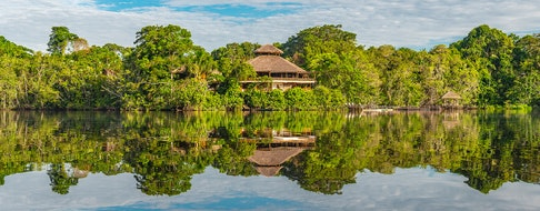 The reflection of an amazon rainforest lodge. The tributaries of the Amazon river comprise the countries of Suriname, Guyana, French Guyana, Venezuela, Colombia, Ecuador, Peru, Bolivia and Brazil