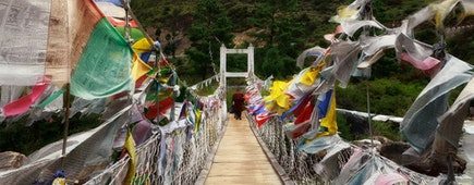 People walk to iron Chain Bridge of Tamchog Lhakhang Monastery, Paro River