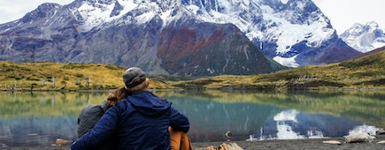 Back of couple next to beautiful mountain lake in Patagonia