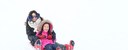 Cute Asian little girl plays sled with her mother in the white and fluffy snow hill in the ski area in Japan