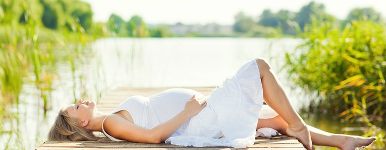 Beautiful pregnant woman relaxing outside