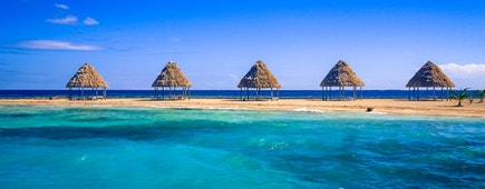 A row of thatched palapas on golden sand on the tiny island of Rendezvous Caye in the Belize Barrier Reef, off the coast of Belize, Central America
