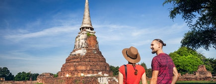 Young Couple in red clothes with photo camera looking at ancient ruined Wat Mahathat in Ayutthaya, Thailand