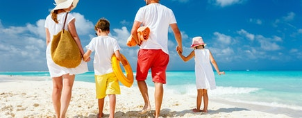 Back view of a happy family at tropical beach on summer vacation