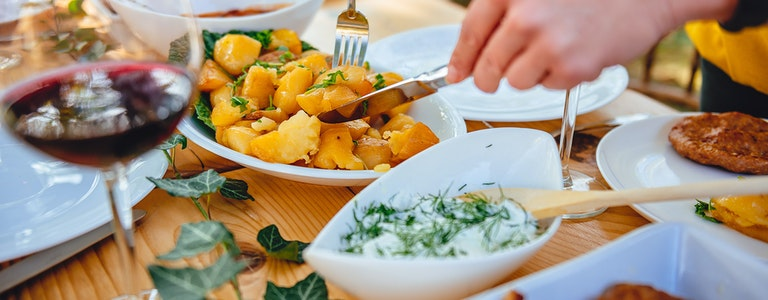 Close up photo of woman serving roasted potato at family lunch in backyard patio