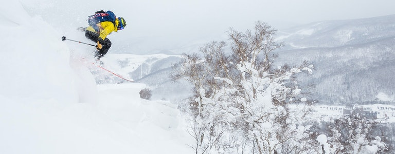 Backcountry skier jumps off a cornice in Hokkaido, Japan. Yellow jacket, blue backpack