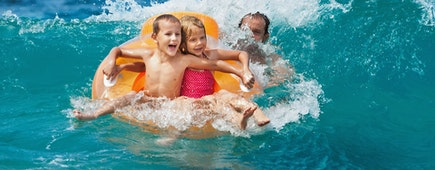 Happy kids have fun in sea surf on beach. Joyful couple of children on inflatable ring ride on breaking wave