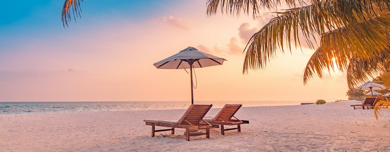 Summer beach landscape. Luxury vacation. Panoramic of sunset beach, two loungers umbrella, palm leaf, colorful sunset sky for paradise island view