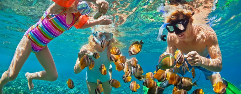 Happy family - mask dive underwater with tropical fishes in coral reef sea pool. summer beach holiday with kids