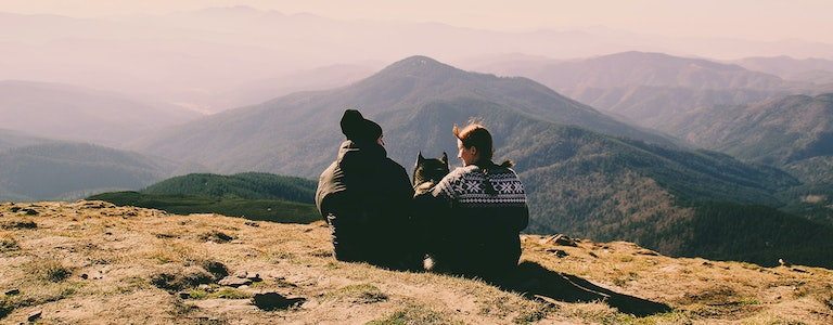 Beautiful couple in the mountains. Autumn. View from the mountain. Necking. Tourists in the hike. Husky dog travel with family