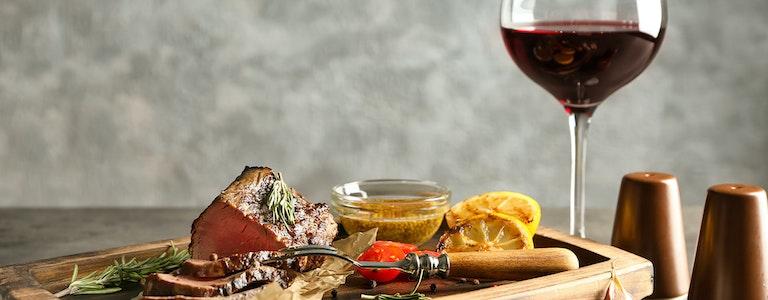 Sliced tasty steak on wooden board