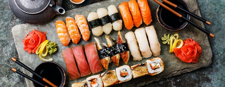 Sushi Set nigiri and sushi rolls with tea served on gray stone slate on metal background