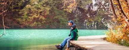 Weekend in autumn park: father with son sit on bridge near the mountain lake