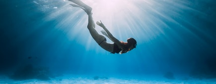 Young woman free diver glides over sandy sea with fins. Freediving in blue ocean