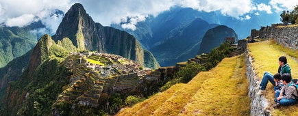 A family group observe the landscape from the platforms in Machupicchu, Peru.