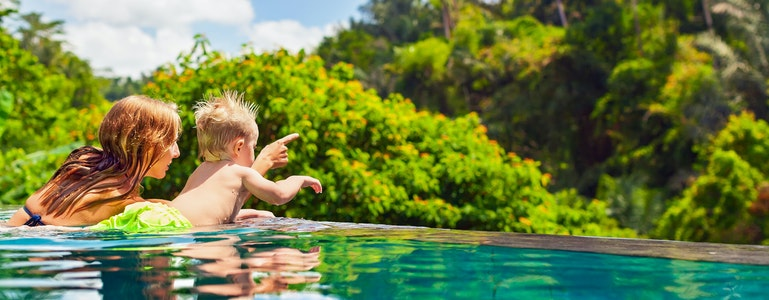 Family Bali beach holiday concept. Happy son with mother - active baby at poolside in infinity swimming pool