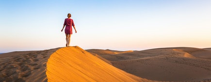 Girl walking on sand dunes in arid desert at sunset and wearing dress, scenic landscape of Sahara or Middle East